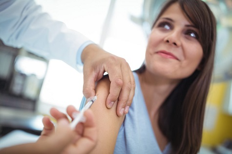 Adult Diabetes. A doctor delivers a shot to a woman with diabetes.